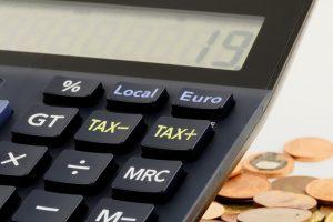 Calculatrice avec pièces de monnaie posées à côté