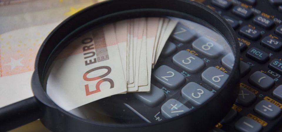 Calculatrice, billets en euros et loupe