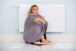 Femme qui a froid et qui est collée au radiateur